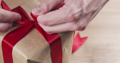Young man hands tying ribbon bow on present box Stock Footage