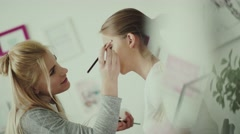 Make-up artist puts a brush for make-up and making feather Stock Footage