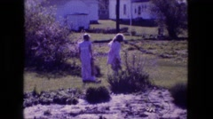 1976: two young blonde, dressed up girls looking into bushes around farmland Stock Footage