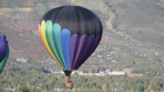 Rainbow colored balloon floating with fall colored mountains in the background Stock Footage