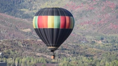 Hot air balloon floating with fall colored foliage in the background Stock Footage