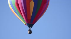 Beautiful brightly colored balloon floating against a blue sky Stock Footage