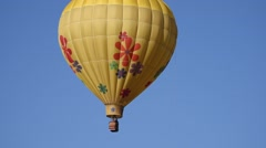 Yellow 70's themed balloon floating against clear blue sky Stock Footage
