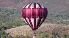 Maroon and silver hot air balloon with fall colored foliage in the background Stock Footage