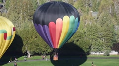 Rainbow colored hot air balloon lifting off in Park City Utah Stock Footage