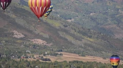 Brightly colored hot air balloons with mountains in the background Stock Footage