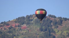 Fall colored balloon floating in the air with fall foliage covered mountains  Stock Footage