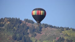 Beautiful black and fall colored hot air balloon floating across a blue sky Stock Footage