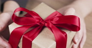 Female teen hands unties the red bow on paper box Stock Footage
