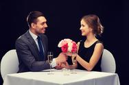 Smiling man giving flower bouquet to woman Stock Photos
