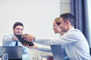 Smiling business people with tablet pc in office Stock Photos