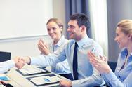 Smiling business team shaking hands in office Stock Photos