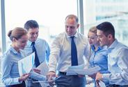 Business people with papers talking in office Stock Photos