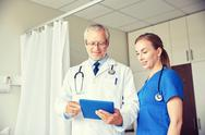 Senior doctor and nurse with tablet pc at hospital Stock Photos