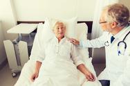 Doctor visiting senior woman at hospital ward Stock Photos