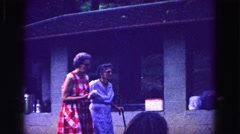1971: grandmothers walking with cane helping each other at summer family reunion Stock Footage