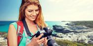 Happy woman with backpack and camera over seashore Stock Photos