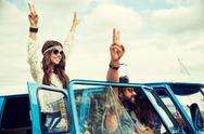 Hippie friends over minivan car showing peace sign Stock Photos
