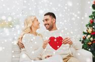 Happy couple with red heart at home for christmas Stock Photos