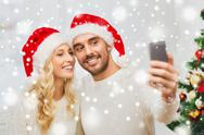 Couple taking selfie with smartphone at christmas Stock Photos