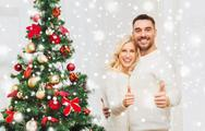 Happy couple showing thumbs up with christmas tree Stock Photos
