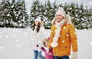 Happy family in winter clothes walking outdoors Stock Photos