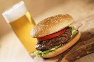 Fresh juicy burger with lager beer on oak table Stock Photos