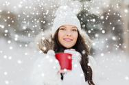 Happy young woman with tea cup outdoors in winter Stock Photos