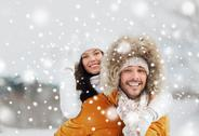 Happy couple having fun over winter background Stock Photos