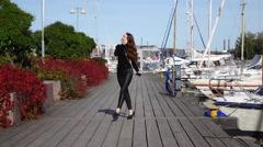 Cheerful girl walk on wooden pier, listen music, nice yacht moorage, positive Stock Footage