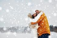 Happy couple hugging and laughing in winter Stock Photos