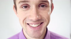 Extreme close-up face of young attractive smiling man in studio on white Stock Footage