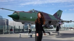 Woman stand against military plane monument, long hair wave on wind, slow motion Arkistovideo