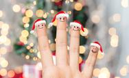 Close up of hand with four fingers in santa hats Stock Photos