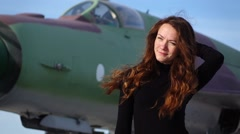 Portrait of brunette woman with long hair against old battle plane, slow motion Stock Footage