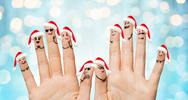 Close up of fingers with smiley in santa hats Stock Photos