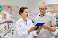 Pharmacist with tablet pc and senior man Stock Photos