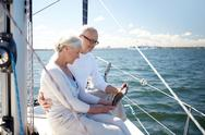Senior couple with tablet pc on sail boat or yacht Stock Photos