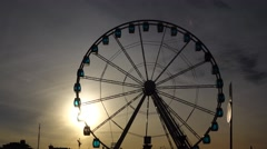 Setting sun shine through empty observation cabins on panoramic wheel Stock Footage