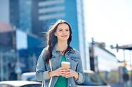 Happy young woman drinking coffee on city street Stock Photos
