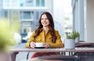 Happy woman drinking cocoa at city street cafe Stock Photos