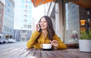 Happy woman calling on smartphone at city cafe Stock Photos