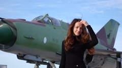 Young woman stand against MiG-21 Fishbed supersonic jet fighter aircraft Arkistovideo