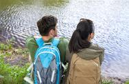 Couple with backpacks sitting on river bank Stock Photos