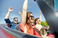 Happy friends driving in cabriolet car at country Stock Photos