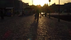 Father with toddler stroll away at sett stony promenade, evening sunlight Stock Footage
