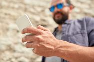 Close up of man with smartphone at stone wall Stock Photos