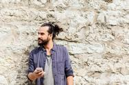 Man with smartphone at stone wall Stock Photos