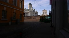 Helsinki Cathedral partly seen from old narrow street, tram pass by Stock Footage
