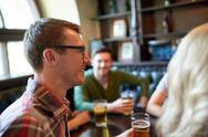Happy man drinking beer with friends at bar or pub Stock Photos
